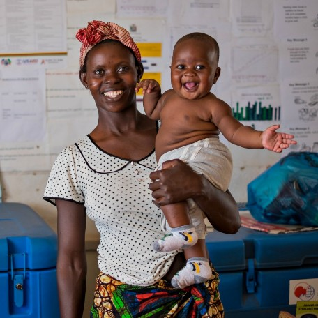 Baby in Zambia smiles with his mother during a medical visit.