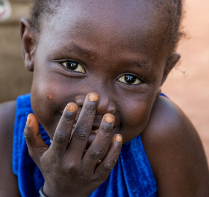 child with hand over mouth smiling gratitude thanksfgiving