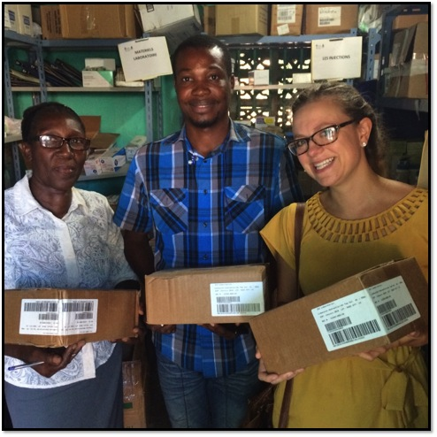 Brittany, a pharmacist volunteering with CMMB, presents the boxes of Lidocaine 4% to the Hospital Alma Mater pharmacy staff.