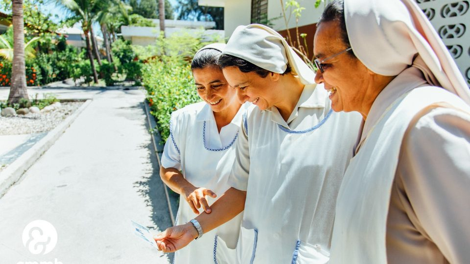 Three sisters look at a picture in Haiti. Weekly reflection sign up