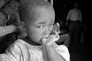 Kenyan child with her thumb in her mouth black and white hungry