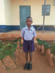 Mwendo John outside of his school. He needs your support to continue his education.