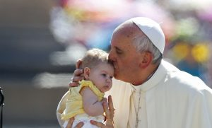 Pope Francis kisses a baby as he arrives to lead the weekly audience in Saint Peter's Square at the Vatican. (Stefano Rellandini/Reuters photo)