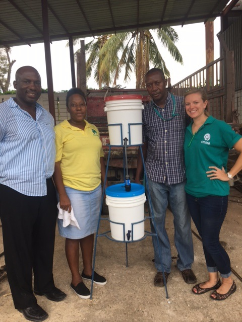 A volunteer and two members of CMMB staff stand beside a fully installed water filtration system.