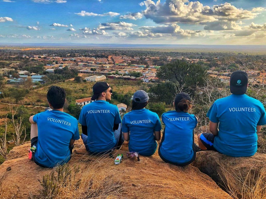 "Thank you to volunteers: CMMB volunteers wear blue shirts while sitting on top of a mountain. They face the landscape and the back of their shirts read, ""volunteer"""