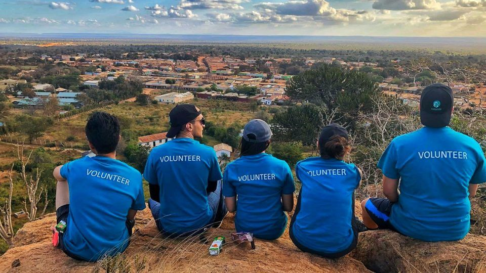 Thank you to volunteers: CMMB volunteers wear blue shirts while sitting on top of a mountain. They face the landscape and the back of their shirts read,