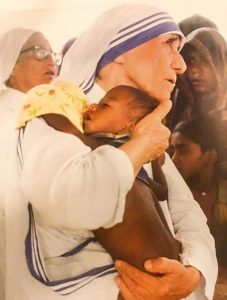 mother teresa holding a baby in her arms