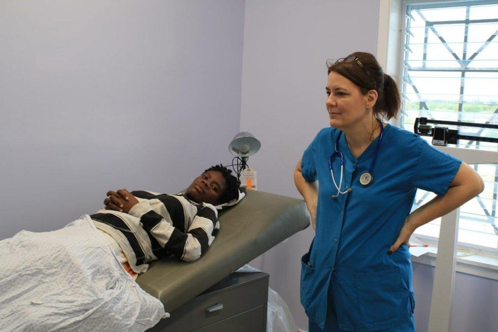 A volunteer stands with a patient at a new hospital in Haiti.