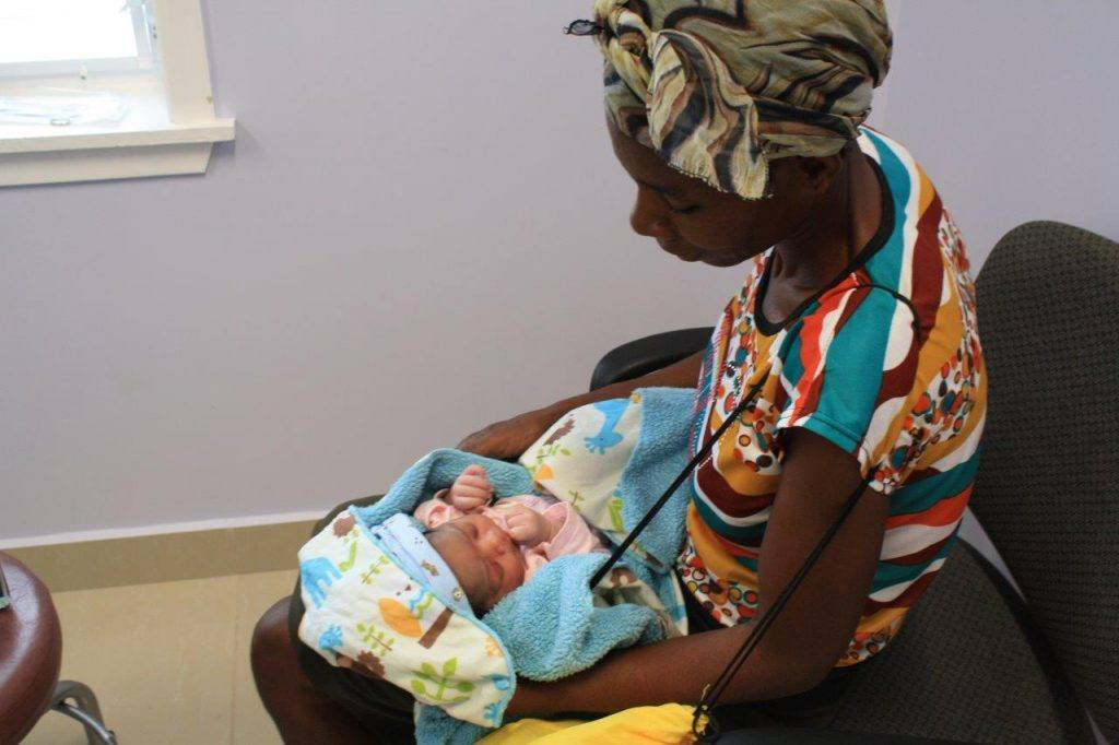 A baby holds in newborn at the opening of a new hospital in Cotes-de-Fer Haiti.