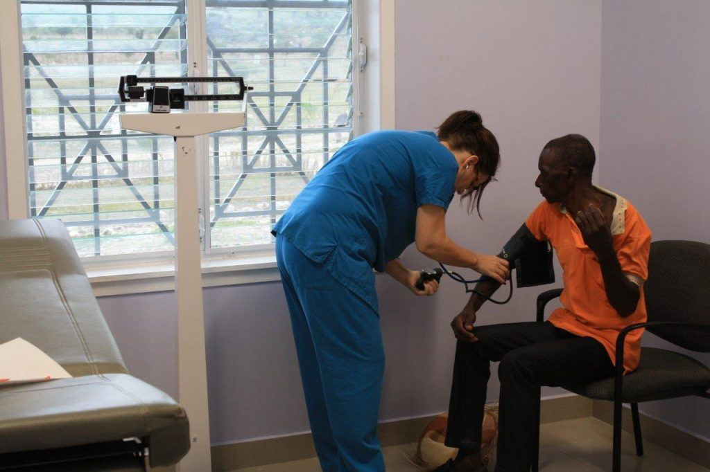 A volunteer takes the blood pressure of one of the patients at a new hospital in Haiti