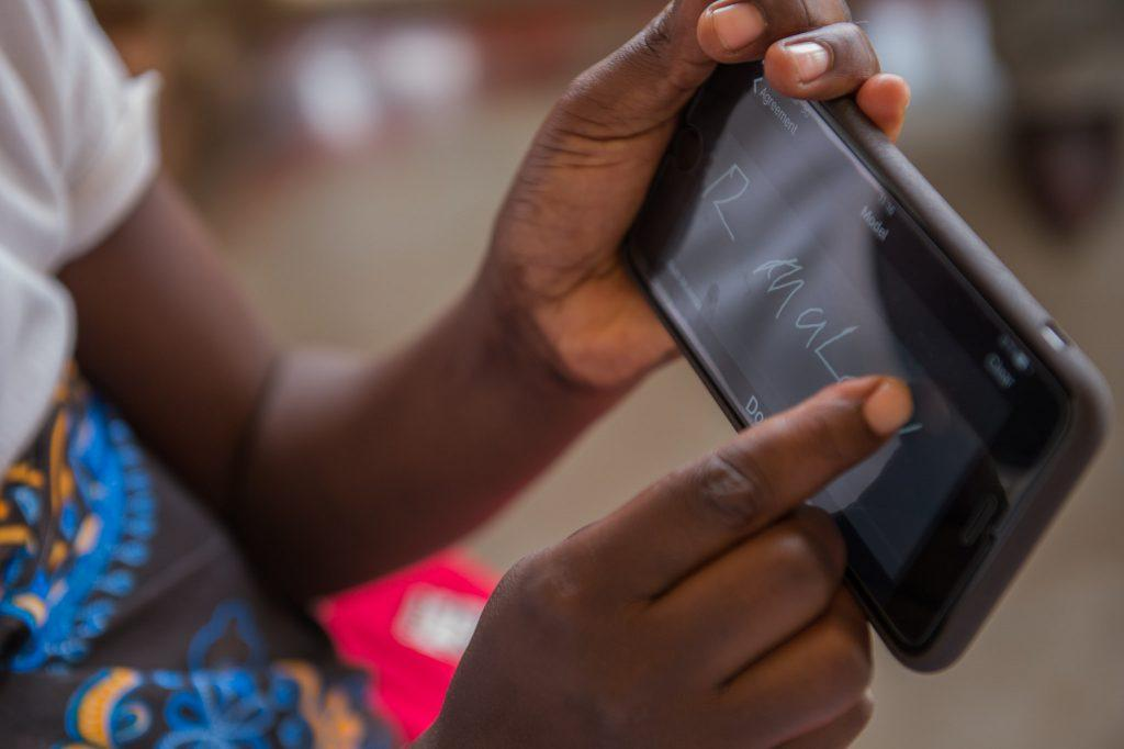 Hands with a mobile phone device. mHealth in Haiti and other developing countries can mean the difference between life and death.