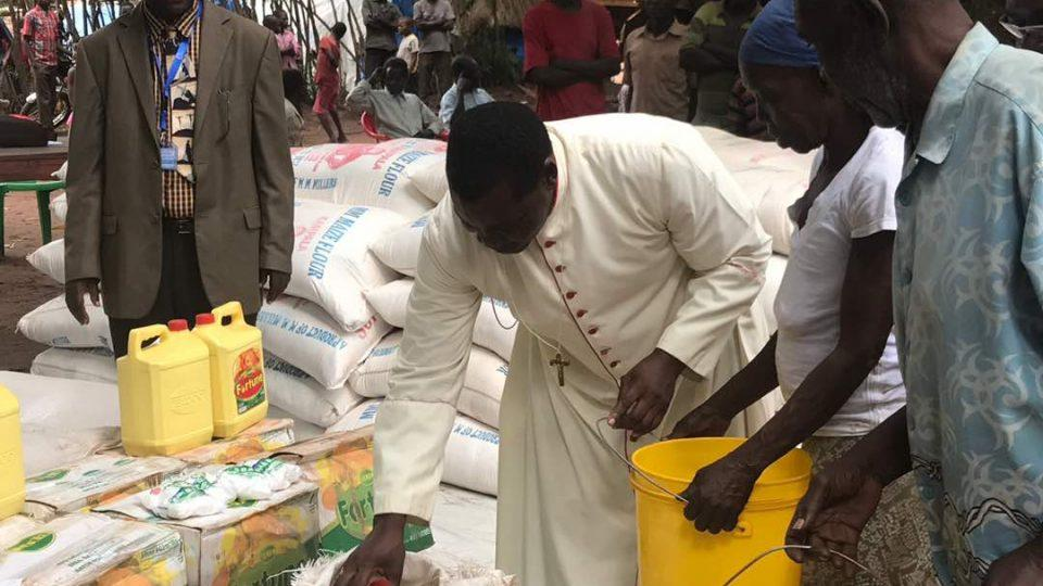 Bishop Eduardo distributes food at the Rimenze camp
