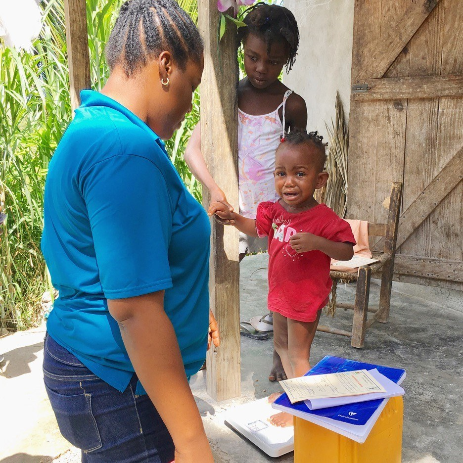 Bedlina stands on the scale to get weighed. She is with Joanna our CMMB project manager in Cotes-de-Fer