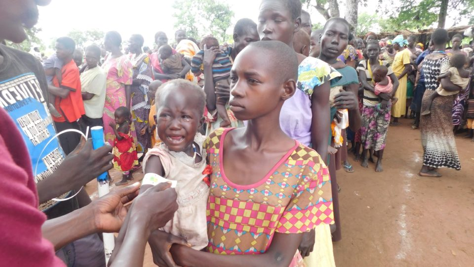 Internally displaced People awaiting for health assessments in South Sudan. Child is crying.