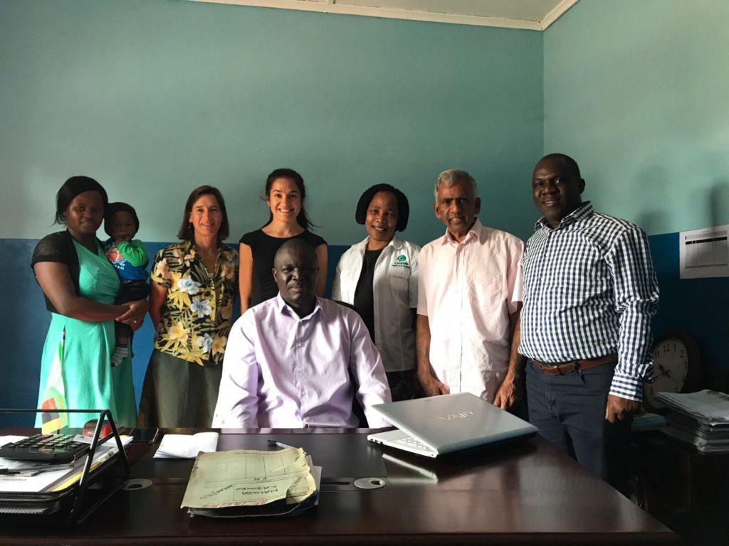 team photo at the district office with Dr. Tembo and local member of the community
