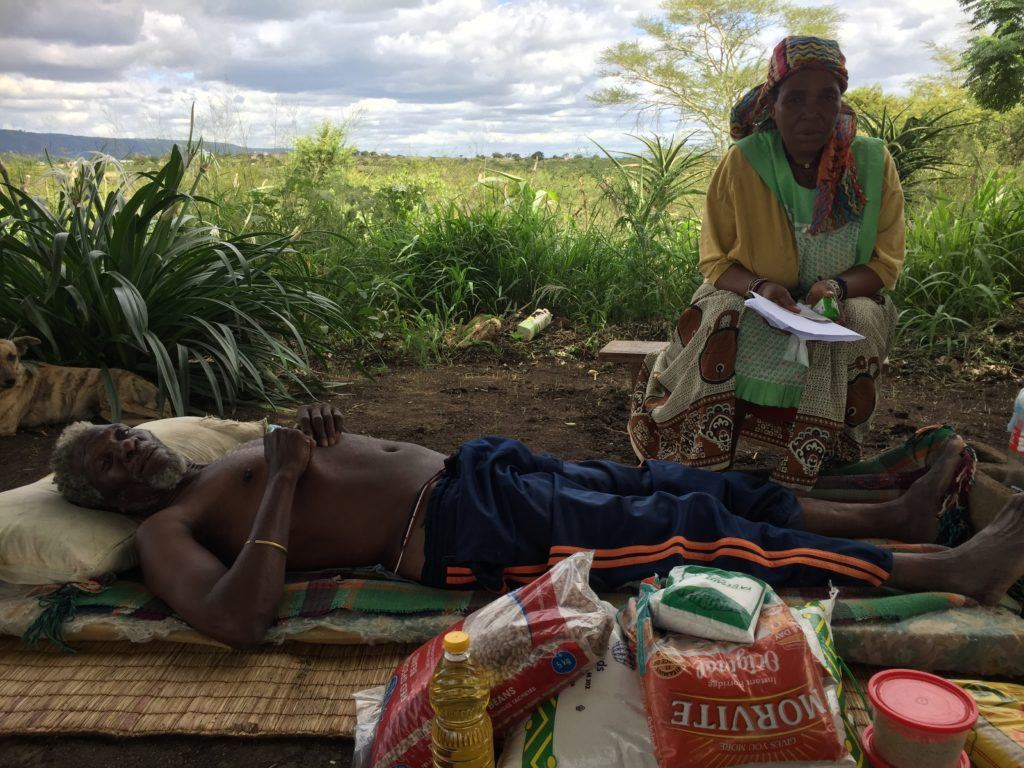 A eSwatini man lies on a reed mat receiving home based care.