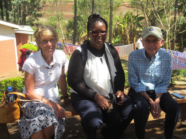 Nurse Kathleen, Phila, and Dr. Al sit on a bench in the shade smiling at the camera. They attended a course in Kenya.