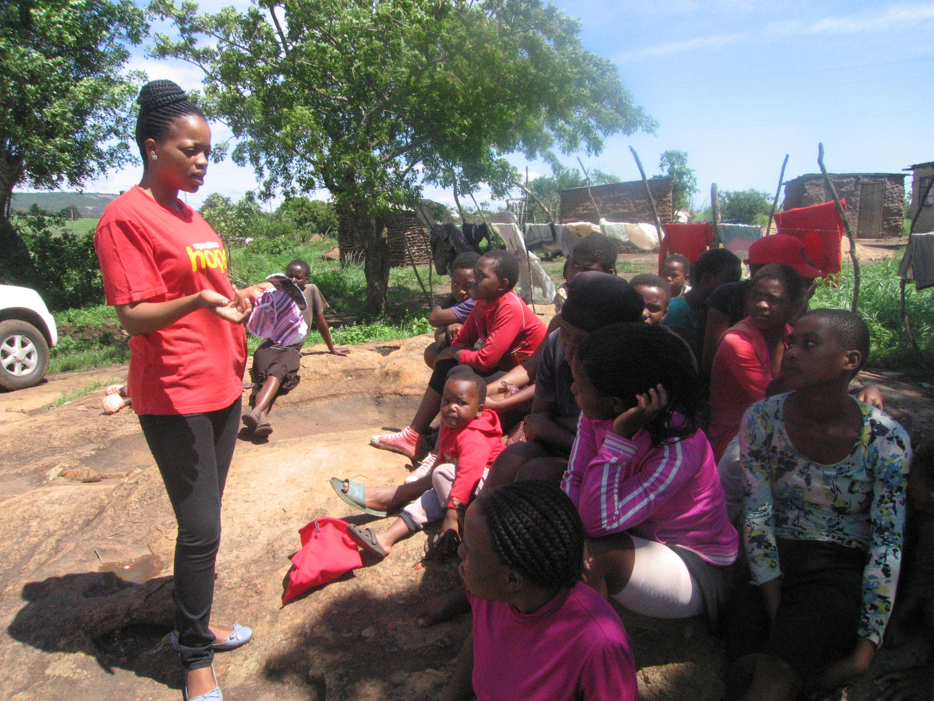 A young woman stands in front of several young girls sharing information about female hygiene.