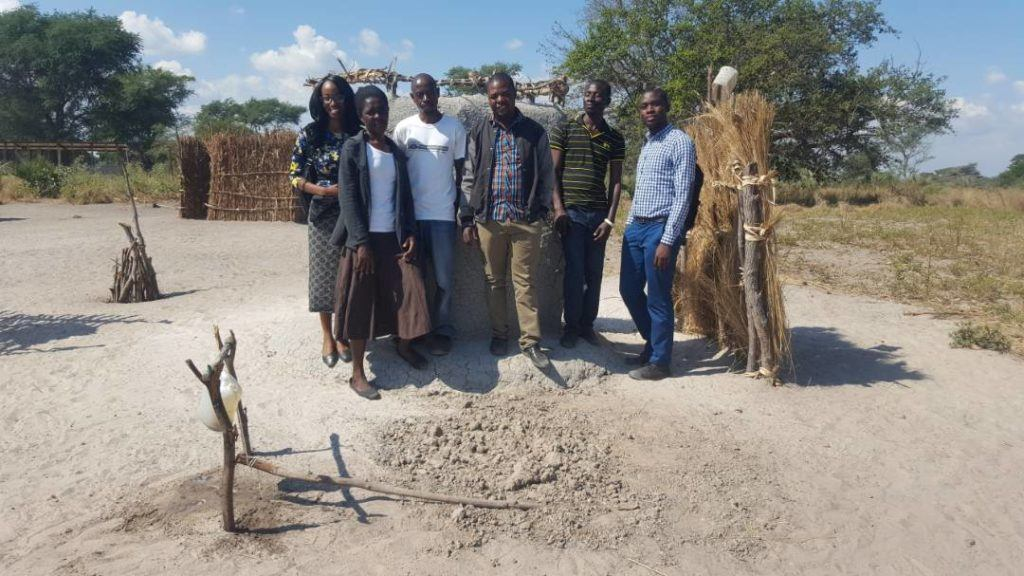 Janet stands with community WASH champions in Zambia
