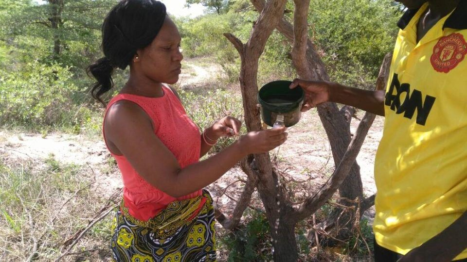 Erica (left) and a WASH Champion Litebelele (right) collect water for testing from the main source used by populations in Likatalelo village.