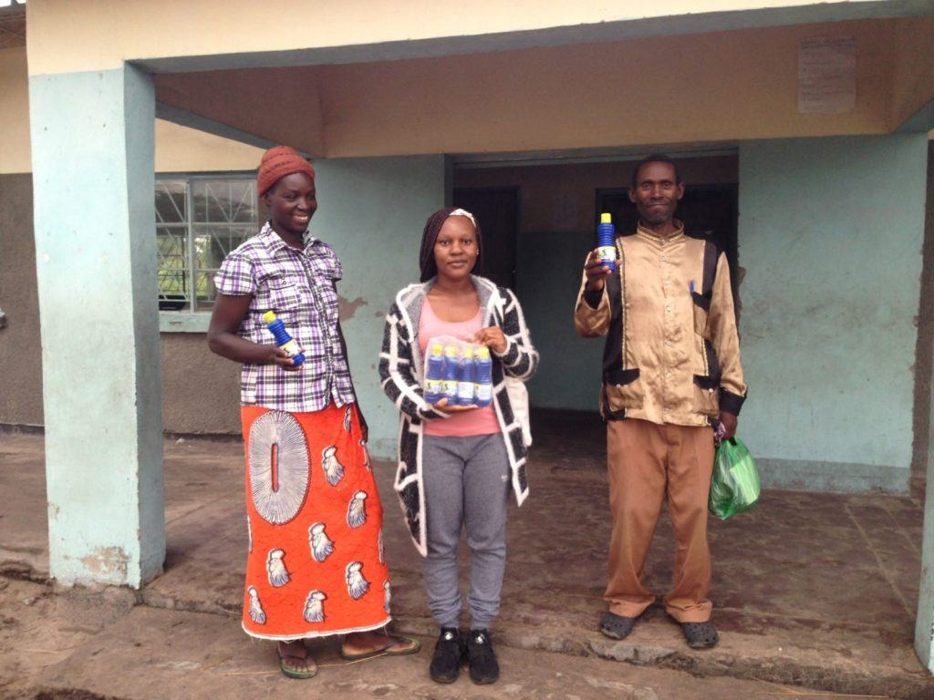 Fig: Erica CMMB Volunteer (middle) stands with community members who procured chlorine for treating water in their homes.
