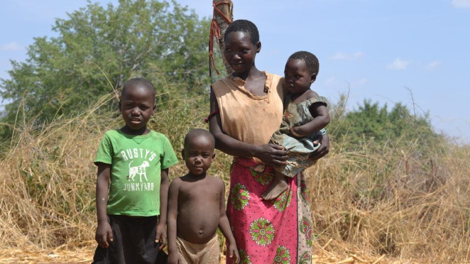 Muthania, mother and her children outside of their home in rural Kenya.