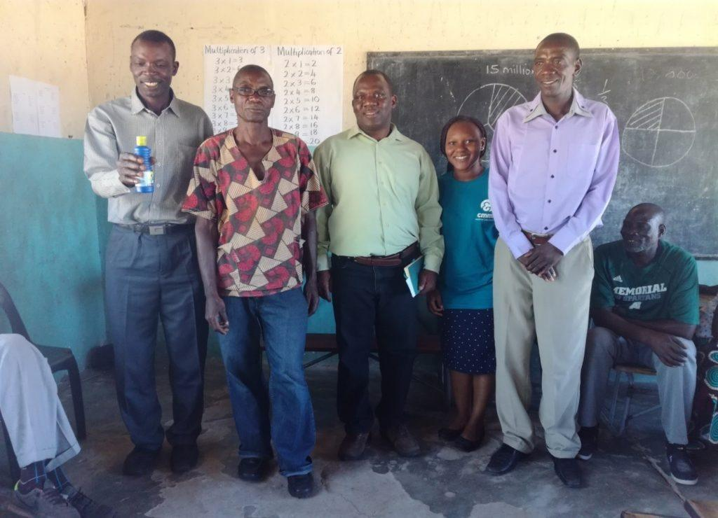 From left to right : Induna Silalo holding a chlorine bottle in  a community meeting, Mr Brian Zuze a WASH Champion, Mr Richard Shimwala CMMB CHAMPs co-ordinator,  Erica CMMB volunteer and Mr Litebelele Kekelwa a WASH Champion during a Chlorine sensitization meeting in Simungoma