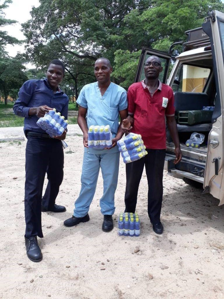 Fig: Nurse in Charge at Matoya rural Health centre (middle) stands with assistant (left) and WASH Champion (right) as they receive the chlorine bottles delivered by CMMB in their community.