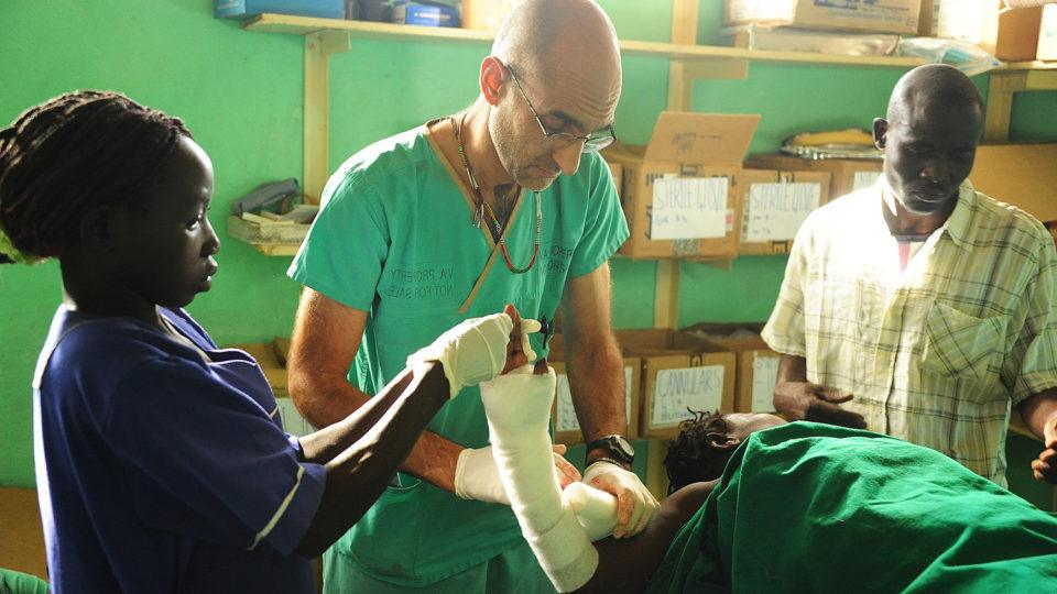 """Dr. Tom Catena wraps a patient's arm during a scene from """"The Heart of Nuba"""" documentary in the Nuba Mountains of Sudan. Catena, a Catholic native of the Diocese of Albany, has served the last 10 years as the only physician at Mother of Mercy Hospital for the region's 1 million people."""