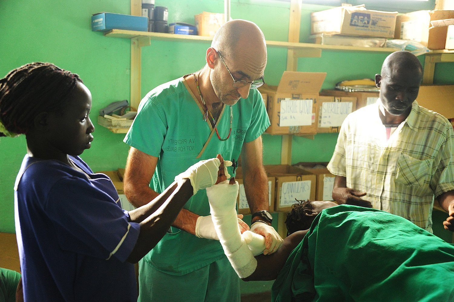 "Dr. Tom Catena wraps a patient's arm during a scene from ""The Heart of Nuba"" documentary in the Nuba Mountains of Sudan. Catena, a Catholic native of the Diocese of Albany, has served the last 10 years as the only physician at Mother of Mercy Hospital for the region's 1 million people."
