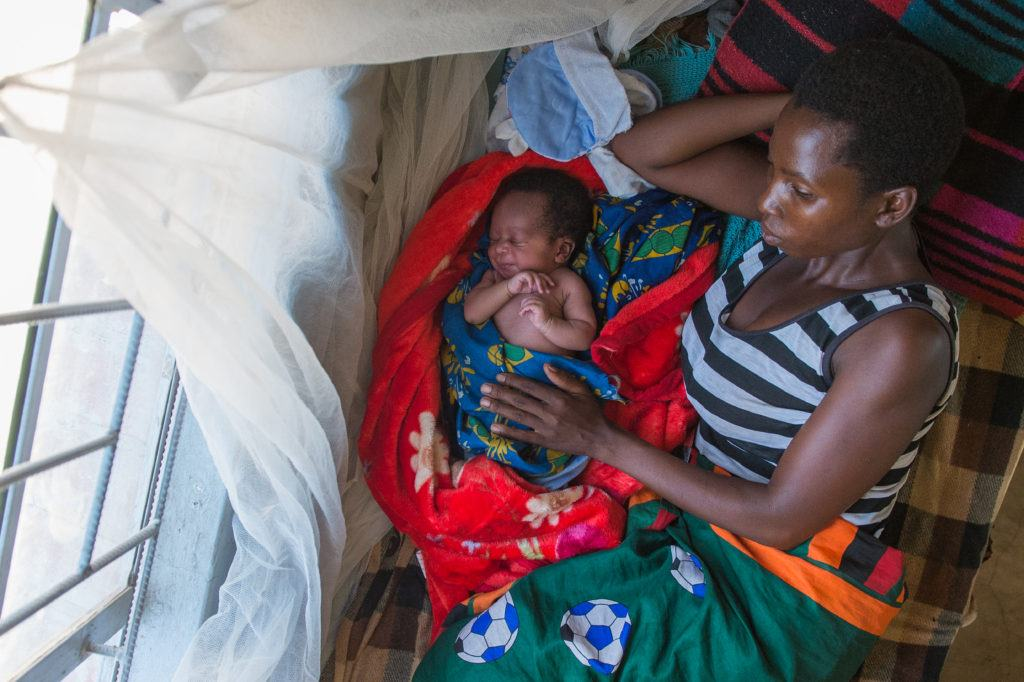 mother lying with infant under malaria net