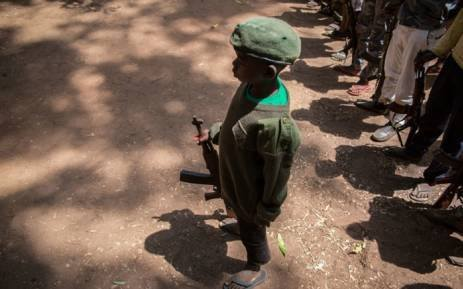 Child soldier standing with his weapon in South Sudan during disarming ceremony