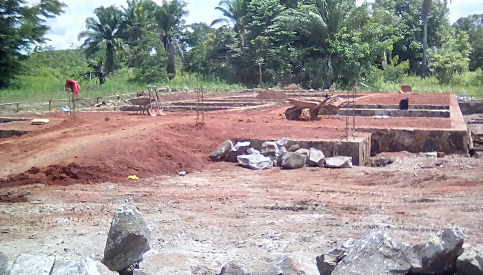 Completion of the back veranda foundation and columns was delayed due to lack of cement. A stone base was laid to support partion walls of the bathrooms and lockers. Backfill of murram soil is in progress