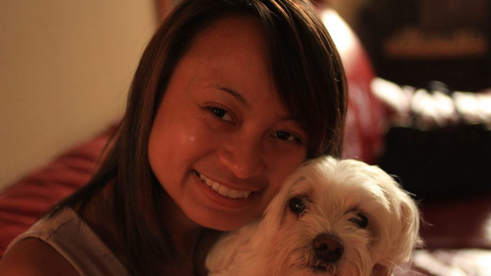 Picture of international volunteer Ellise Carlos with a dog. She will be serving as a registered nurse in Kenya.