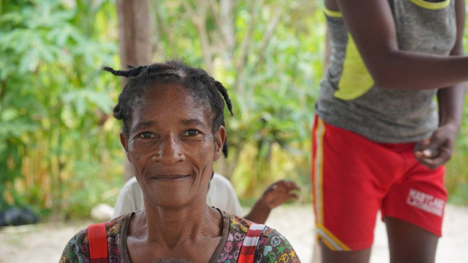 Joceline's home is in bad shape so they are outside in Haiti. She is a grandmother.