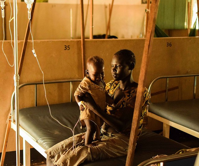 Mother holding child who is being treated for malaria