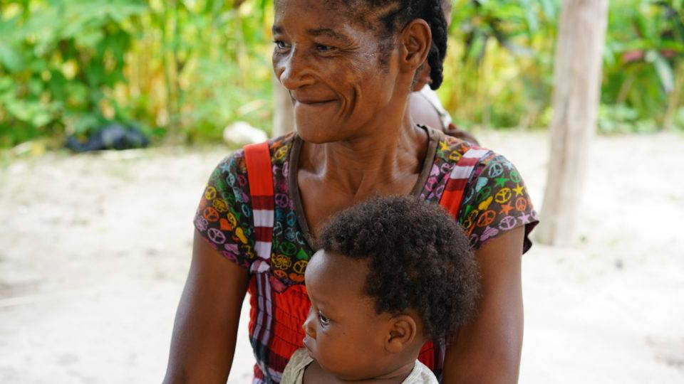 Joceline has 8 kids. She is Technaida's grandma. They are outside in Haiti because their home is in bad shape.