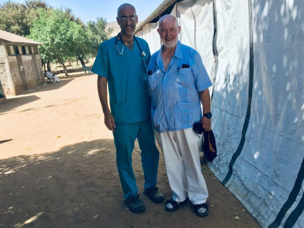Dr. Tom with Dr. Harry in South Sudan. They stand in the shade outside.