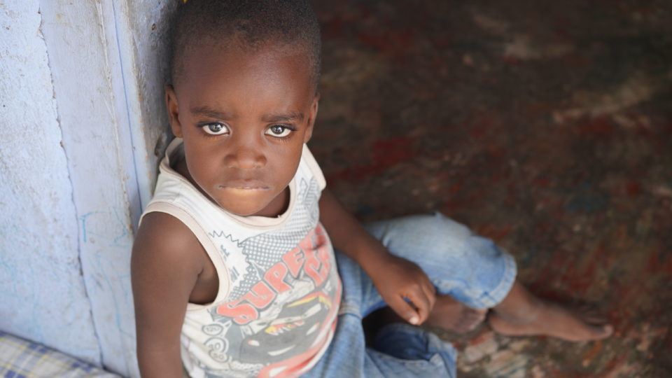 Jeffrey sitting in the doorway of his home in Haiti. He needs an Angel Investor for food and water.