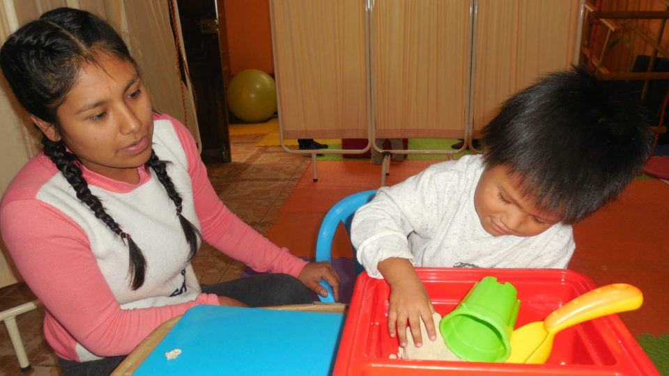 Jordan, playing a game during therapy - CMMB Peru Angel
