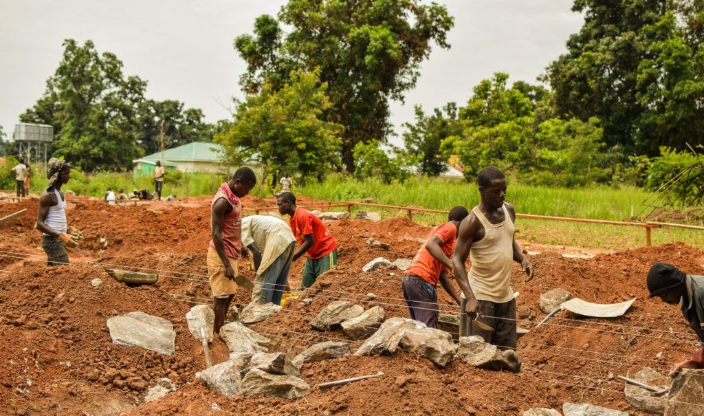 Group of men working at the expansion of St. Theresa Hospital in Nzara.