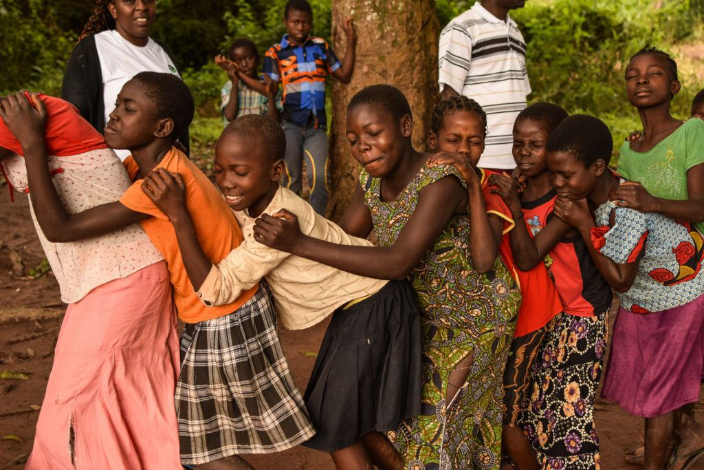 The children are holding each other's shoulders as part of a game during CFS activities.