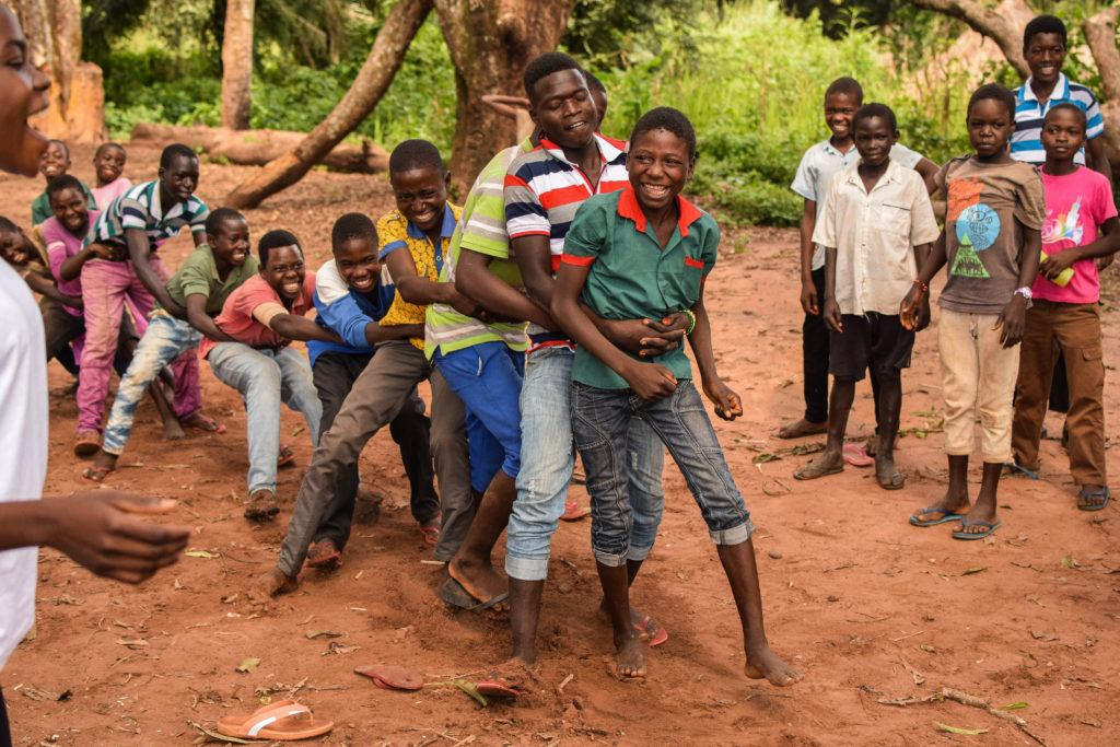 Children play a game of human tug of war. Child friendly spaces bring joy to those living in conflict.