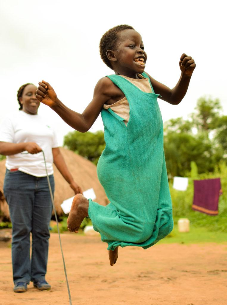 A girl in South Sudan is jumping rope. She is jumping for joy.