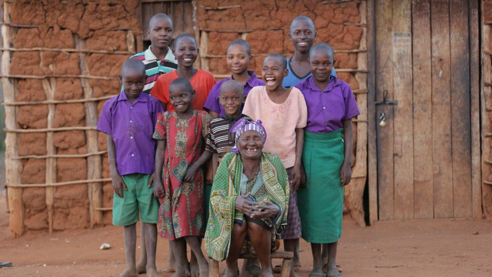 Grandma Grace and her grandchildren in front of their mud home