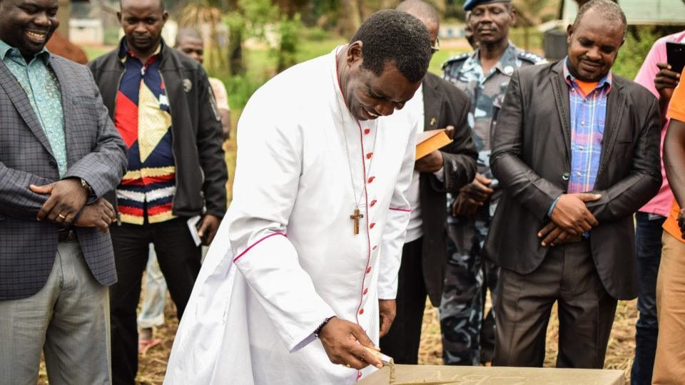 Bishop Eduardo signs the first brick as the construction process begins