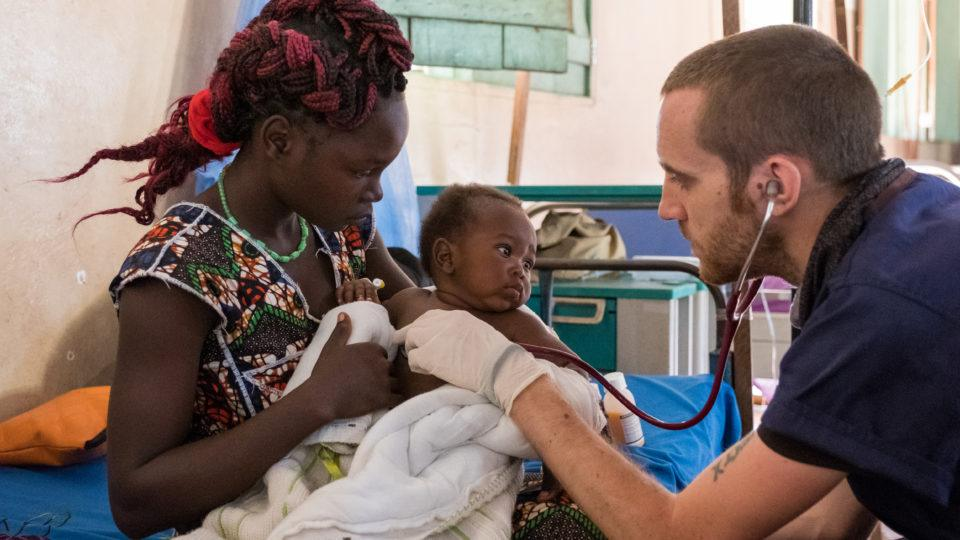 Dr. Matt checks on a baby it's mother's arsm