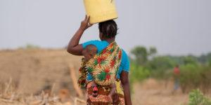 A woman carries her baby and a bucket of water in Mwandi, Zambia