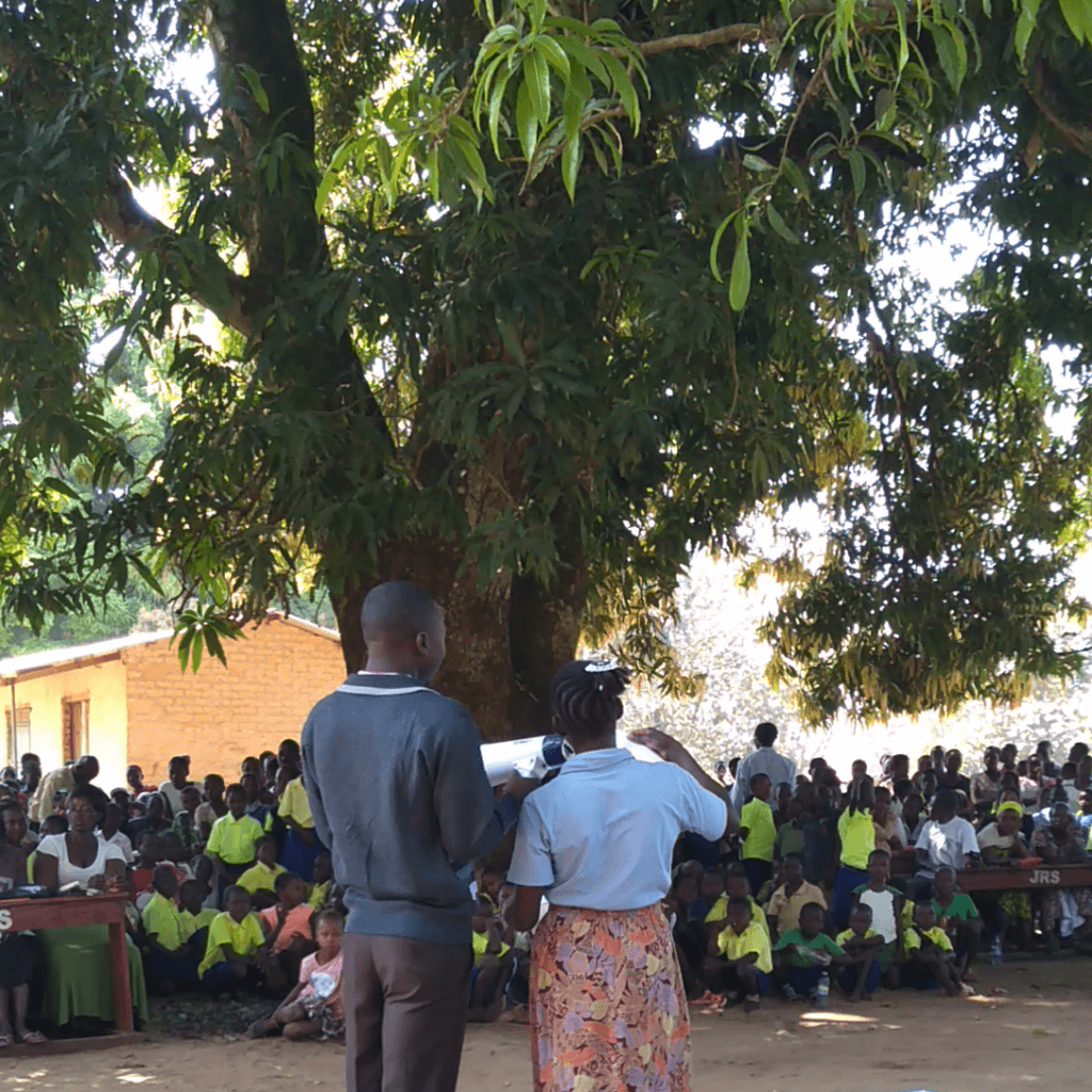 Flora (right) reads out her students' results at the closing of the 2018 term