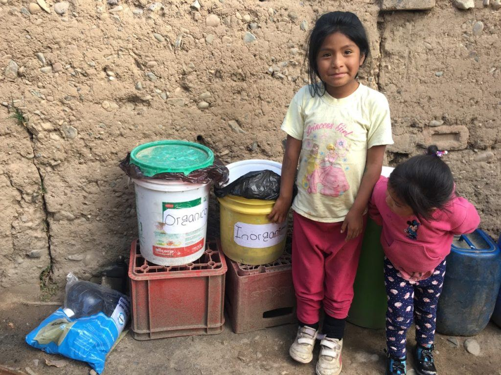 Two of Marcelina's seven children showing their new garbage bins.
